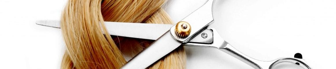 Hairdresser's scissors with strand of blonde hair, isolated on w